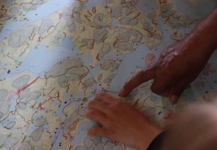 Joseph Ottawa, aîné atikamekw nehirowisiw  de 81 ans ayant participé au projet matakan depuis  le début, montre aux jeunes sur une carte, différents endroits du Nitaskinan avec les histoires qui y sont associé. Photo : Étienne Levac, 2020